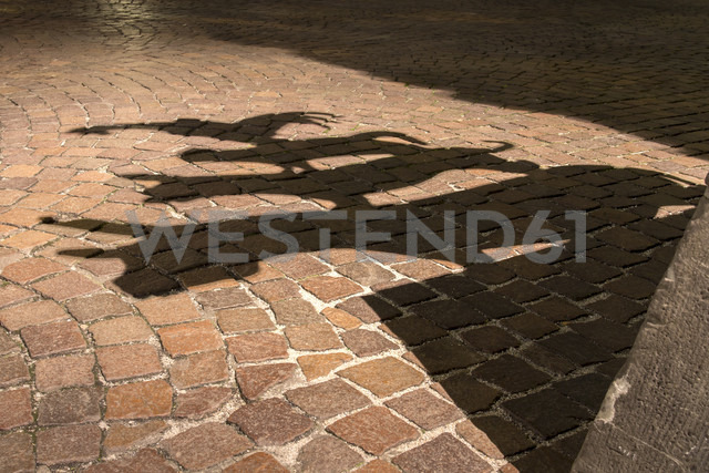 Germany, Bremen, Shadow of the sculpture of the Bremen city minstrels - NKF000070