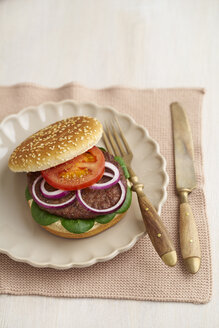 Burger with mincemeat, tomato, lamb's lettuce and red onions on plate - ECF000446
