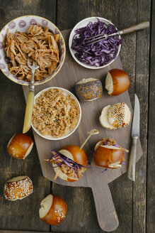 Mini-Burger with pulled pork, red cabbage and fried onions on chopping board - ECF000467