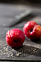 Two Chinese plums (Prunus salicina) on dark wooden table - MAEF008221