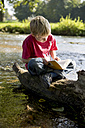 Boy sitting on dead wood at brook reading a book - SARF000400