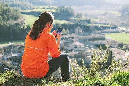 Spain, Catalunya, Orista, young female jogger having a break using smartphone - EBSF000095