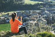Spain, Catalunya, Orista, young female jogger having a break photographing with smartphone - EBSF000096