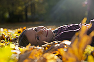 Portrait of smiling little girl lying on autumn leaves in park - SARF000401