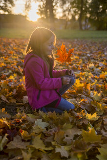 Little girl crouching in between autumn leaves in park - SARF000370