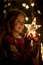 Portrait of smiling little girl holding lighted star of fairy lights - SARF000373