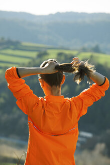 Young female jogger putting her ponytail in order - EBSF000116