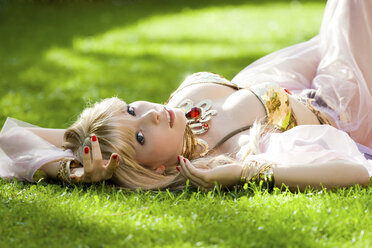 Woman wearing belly dance costume lying in grass - AFF000039