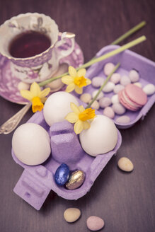 Laid table with cup of tea, daffodils (Narcissus pseudonarcissus), egg carton of macaron, three eggs and sweets on wooden table - VTF000167