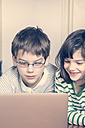 Portrait of brother and sister using laptop at home - LVF000844