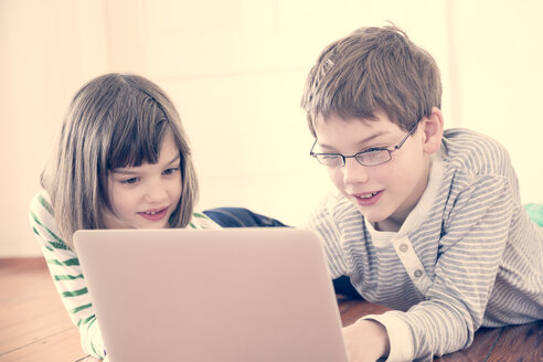 Portrait of brother and sister using laptop at home - LVF000842