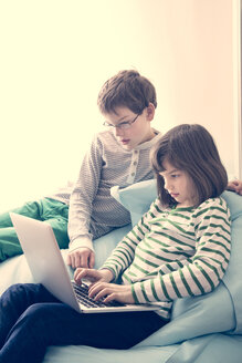 Brother and sister using laptop at home - LVF000897