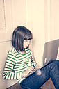 Portrait of little girl using laptop at home - LVF000900