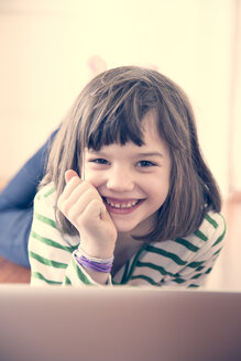 Portrait of smiling little girl with laptop at home - LVF000902