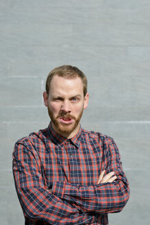 Portrait of angry young man wearing checkered shirt - BR000161