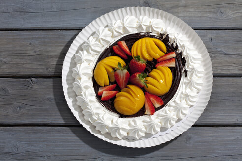 Meringue baked pastry case with chocolate icing garnished with  strawberries and peaches on paper plate and grey wood - CSF021045
