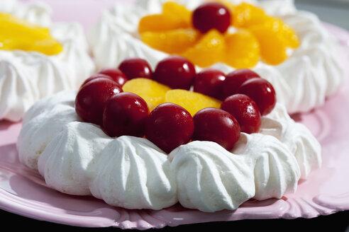 Three garnished meringue tartlets on pink cake plate, close-up - CSF021053