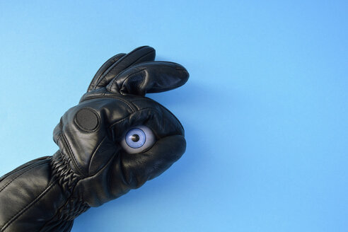 Leather glove and plastic eyeball in front of blue background - AXF000639