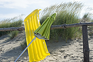 Italy, Adria, air bed and beach umbrella leaning at wooden fence at beach dunes - ASF005281