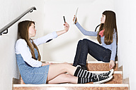Two teenage girls sitting on stairs using smartphone and digital tablet - MAEF008282