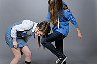 Teenage girl kicking her sister - MAEF008292