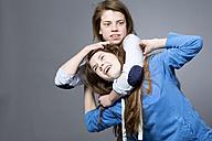Teenage girl having her sister in headlock - MAEF008293