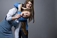 Teenage girl having her screaming sister in headlock - MAEF008247