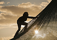 Denmark, Jutland, Vejers, climbing boy at sunset - JBF000089