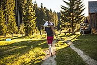 Austria, Gosau, man carrying sticks on rural path - KV000095