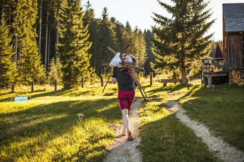 Austria, Gosau, man carrying sticks on rural path - KV000095