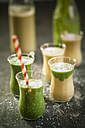 Glasses of spinach smoothie and mango smoothie with desiccated coconut on wooden table - SBDF000652