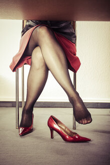 Crossed legs of woman with extravagant red pumps - KRP000381