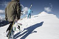 Austria, Vorarlberg, Riezlern, Skier and snowboarder walking uphill - MUM000061
