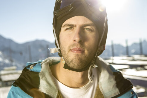Austria, Vorarlberg, Riezlern, Portrait of young man wearing ski goggles - MUMF000067