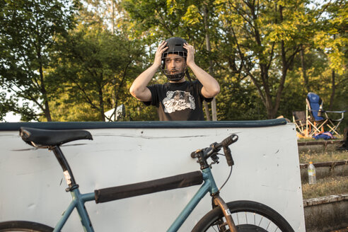 Germany, Hannover, Bike polo player putting on helmet - MUMF000076