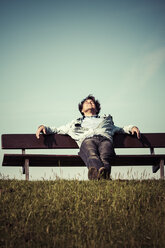 Germany, Hamburg, man relaxing on bench at dyke - KRP000399