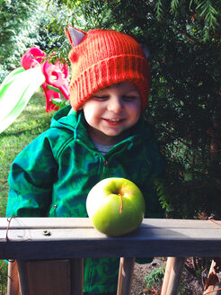 little boy with red hat laughing and looking at apple - AFF000047