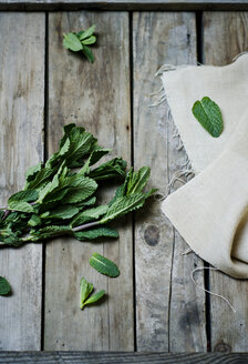 Fresh peppermint and cloth on wooden table, view from above - CZF000140