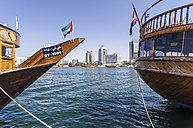 United Arab Emirates, Dubai, Moored ships with skyline of city center in background - THA000178