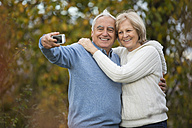 Portrait of happy senior couple taking self-portrait with smartphone - WESTF019213