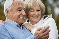 Portrait of smiling senior couple looking self-portrait at smartphone - WESTF019216