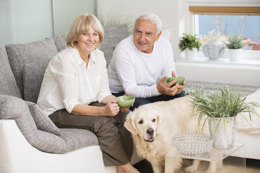 Senior couple sitting side by side on sofa in living room, dog in the foreground - WESTF019234