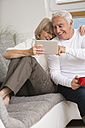 Senior couple with digital tablet side by side on sofa in living room - WESTF019243