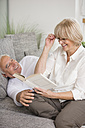 Smiling senior couple with book on sofa in living room - WESTF019249
