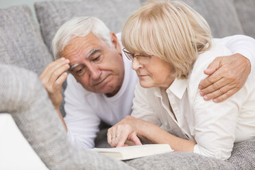 Senior couple with book lying side by side on sofa - WESTF019252