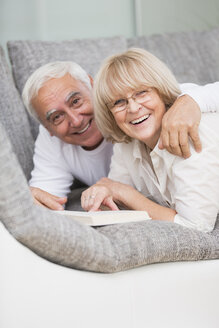 Portrait of smiling senior couple with book lying side by side on sofa - WESTF019255