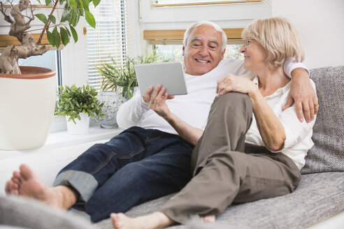 Senior couple with digital tablet side by side on sofa in living room - WESTF019258