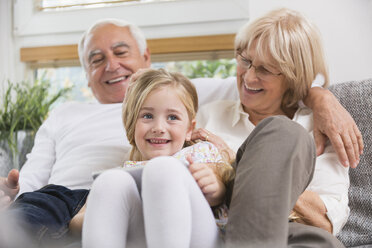 Senior couple and granddaughter sitting with digital tablet on sofa in living room - WESTF019183