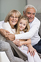 Portrait of senior couple with granddaughter on sofa in living room - WESTF019168