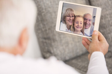 Senior looking at digital tablet with family portrait - WESTF019162
